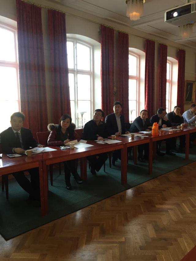Delegationens ledamöter lyssnar intresserat och antecknar