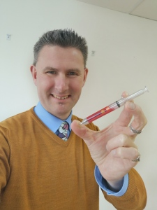 Jag håller pennan som ser ut som en spruta End Polio Now