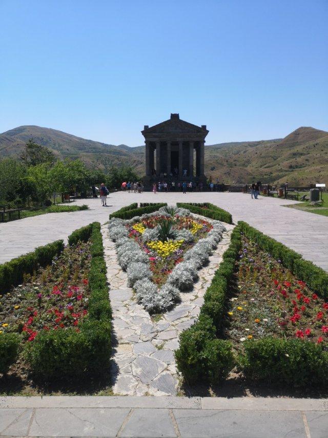 Framför den fyrkantiga tempelbyggnaden finns en plantering. I bakgrunden syns bergslandskapet.