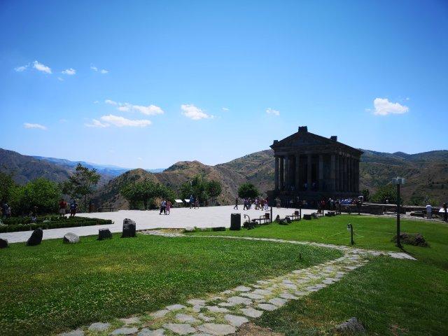 Templet i Garni mot en blå himmel och de gröna bergen i bakgrunden