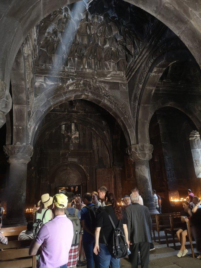 Kyrkan som är mörk innuti lyses upp av en strimma ljus från ett hål i taket